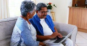 Senior couple using laptop in living room 4k stock video