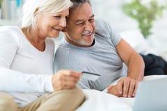 Senior couple using laptop. Loving senior couple at home Stock Image