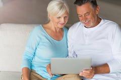 Senior couple using laptop. Loving senior couple at home Stock Photography