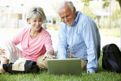 Senior couple using laptop outdoors Royalty Free Stock Photography