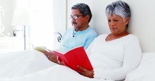 Senior couple using laptop 4 reading book 4k. Senior couple using laptop 4 reading book in bedroom 4k stock video