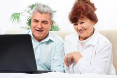Senior couple using laptop sitting sofa Stock Images