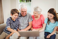 Senior couple using laptop with their grand children Stock Photography