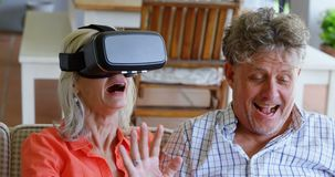 Senior couple using laptop and virtual reality headset on sofa 4k stock video footage