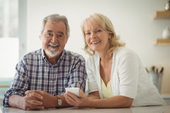 Senior couple using mobile phone in the kitchen. Portrait of senior couple using mobile phone in the kitchen Royalty Free Stock Photos