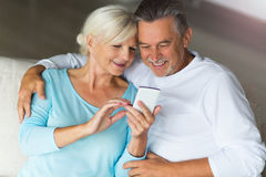 Senior couple using mobile phone. Loving senior couple at home Royalty Free Stock Image