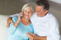 Senior couple using mobile phone. Loving senior couple at home Royalty Free Stock Photography