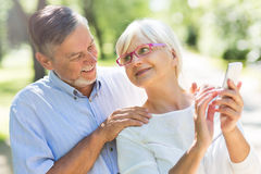 Senior couple using mobile phone. Loving senior couple standing outdoors Royalty Free Stock Photography