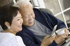 Senior couple using mobile phone outdoors Royalty Free Stock Image