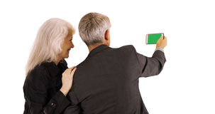 Senior couple using smartphone with green screen on white background Stock Photography