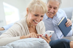 Senior couple using smartphone and laughing Royalty Free Stock Photos