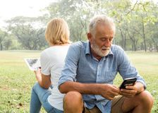 Senior couple using smartphone, People hands addicted by mobile smart phone - Technology concept with connected men and women.  stock photo