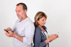 Senior couple using smartphones isolated Stock Photos