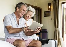 Senior couple using a tablet on the bed royalty free stock photo