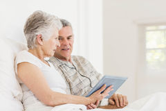 Senior couple using tablet on bed Royalty Free Stock Image