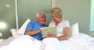 Senior couple using tablet pc. In bed stock footage