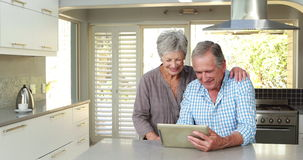 Senior couple using tablet pc. In kitchen stock footage