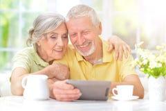 Senior couple using tablet. Portrait of a happy senior couple using digital tablet Royalty Free Stock Photos