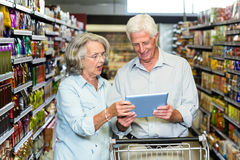 Senior couple using tablet at the supermarket Royalty Free Stock Images