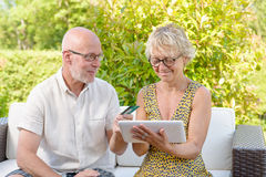Senior couple using tablet to make a purchase. Outside royalty free stock images