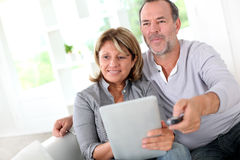 Senior couple using tablet and watching tv Stock Photography