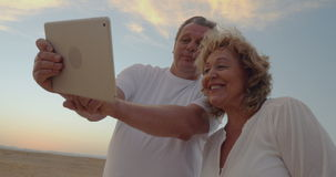 Senior couple using touch pad outdoor on vacation stock footage