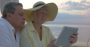 Senior couple using touch pad at the seaside stock video footage