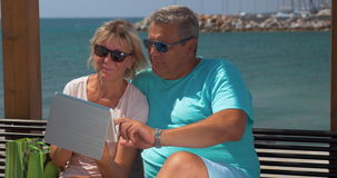 Senior couple using touch pad on waterfront stock video footage