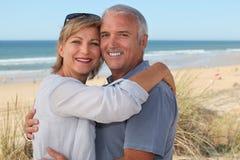 Senior couple on vacation embracing Stock Photos