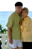Senior couple vacation portrait. A senior couple outdoors by the ocean royalty free stock image