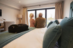 Senior Couple On Vacation Sitting On Hotel Bed Stock Photography