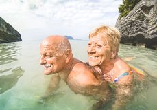 Senior couple vacationer having genuine playful fun on tropical beach royalty free stock images