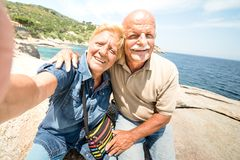 Senior couple vacationer taking selfie while having genuine fun at Giglio Island - Excursion tour in seaside scenario. Active elderly and travel concept stock photo