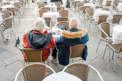 Senior couple. Venice, Italy - February 27, 2017: Senior couple sitting at the tables of a cafe in Venice, Italy Royalty Free Stock Photo