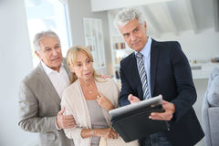 Senior couple visiting new house with real-estate agent Stock Photography