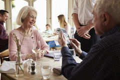 Senior Couple With Waiter Paying Bill In Restaurant Royalty Free Stock Images