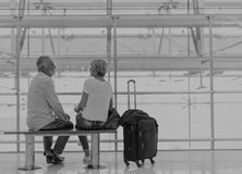 Senior couple waiting for boarding inside airport Stock Photos