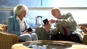 Senior couple waiting for flight. Senior couple of tourists waiting for their flight sitting with suitcase and talking stock footage