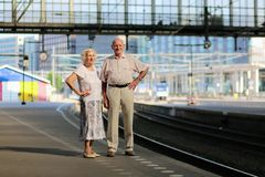 Senior couple waiting for train at railway station. Happy senior caucasian couple travelling around Europe waiting for train in railway station platform in stock image