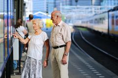Senior couple waiting for train at railway station. Happy senior caucasian couple travelling around Europe waiting for train in railway station platform in royalty free stock images