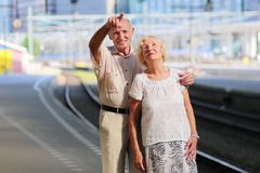 Senior couple waiting for train at railway station. Happy senior caucasian couple travelling around Europe waiting for train in railway station platform in royalty free stock image