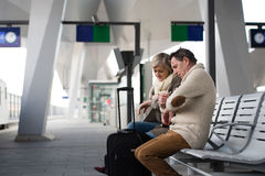 Senior couple waiting on train station, looking at watch. Royalty Free Stock Photo