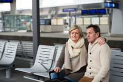 Senior couple waiting on train station, looking at watch. Stock Photography