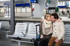 Senior couple waiting on train station, sitting on bench, kissin Stock Image