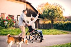 Senior couple with wheelchair on a walk with dog. Stock Photography