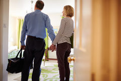 Senior couple walk in to hotel room holding hands, back view stock photography