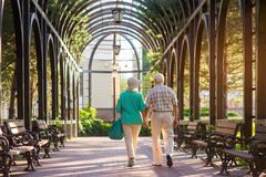 Senior couple walking on alley. Two people holding hands. Love is gift of life. Thank those who support us Royalty Free Stock Image