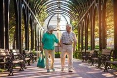 Senior couple walking along alley. Stock Photos