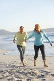 Senior Couple Walking Along Beach Stock Photography