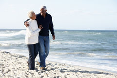 Senior Couple Walking Along Beach Together royalty free stock images